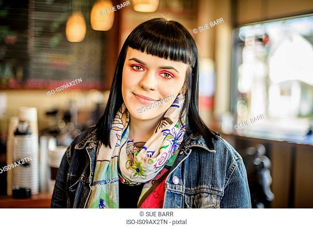 Woman in coffee shop looking at camera smiling