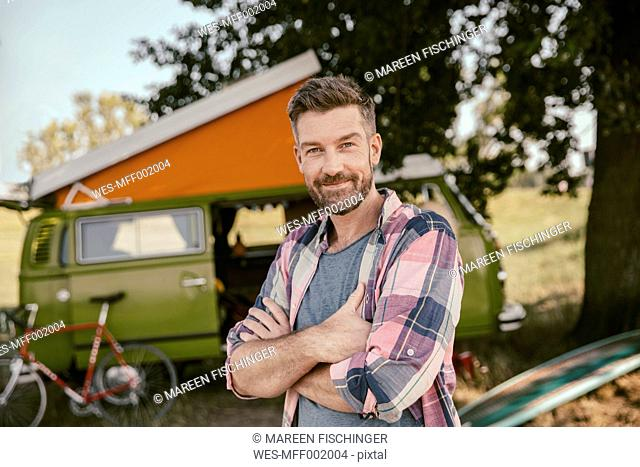 Smiling man in front of van in the nature