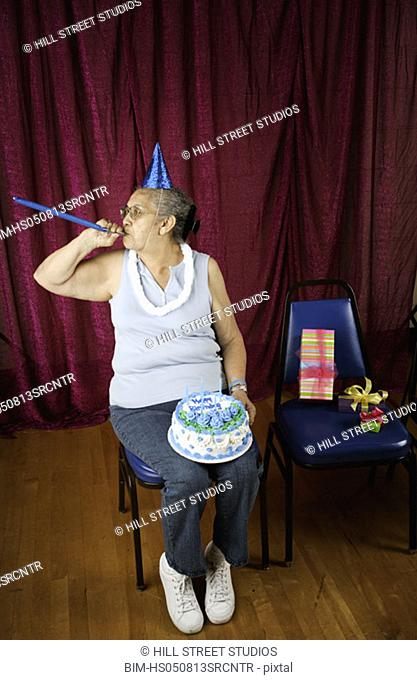 Woman with party favors and birthday cake