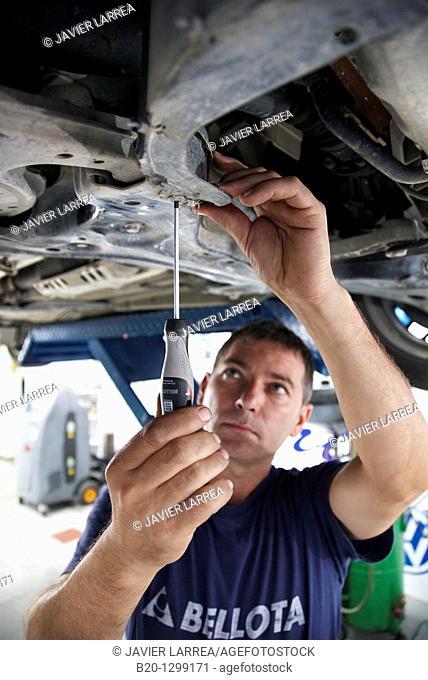 Worker using screwdriver in car repair shop