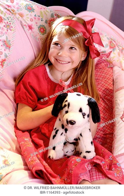Little girl wearing a romantic red dress sitting on her bed and playing with a stuffed toy dog