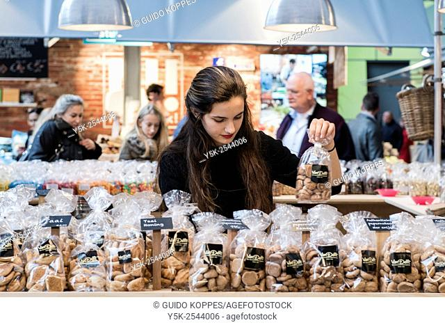 Rotterdam, Netherlands. Attractive brunette female sorting out little bags with candy in her Markthall market stall