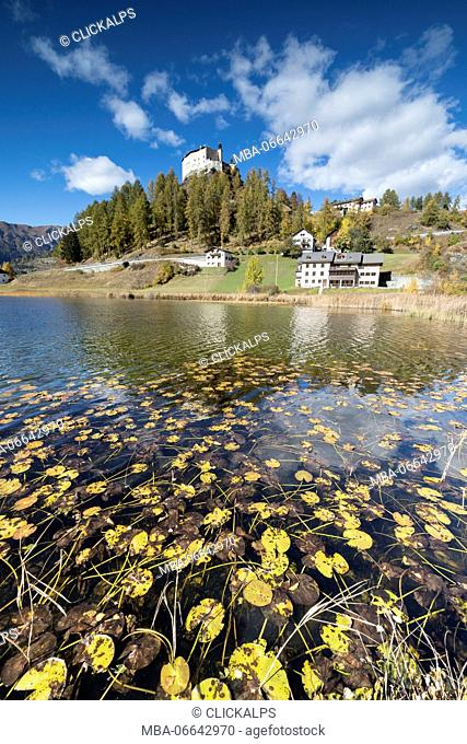 Autumnal leaves fallen in Lake Tarasp frame the old castle Inn district Canton of Graubünden Engadine Switzerland Europe