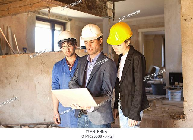 A building contractor and architects looking at a laptop at a building site