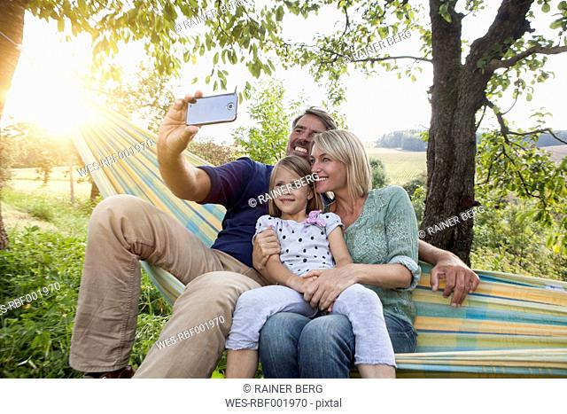 Happy family taking selfie in hammock