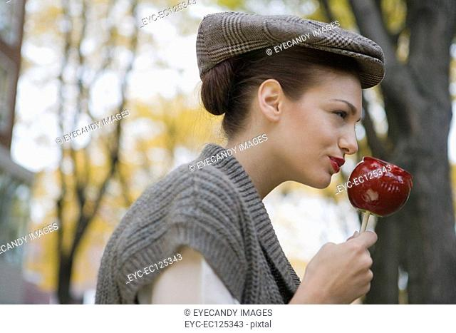 Profile of young woman eating candy apple