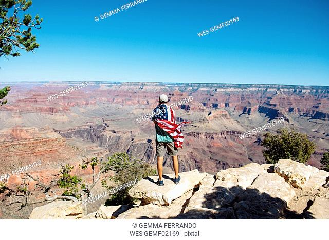 USA, Arizona, back view of man wrapped in American flag enjoying view of Grand Canyon National Park