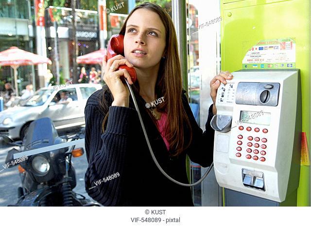 junge Frau beim Telefonieren in Telefonzelle und gestikuliert ³berlegt schaut sehnsuechtig. - Austria, 25/07/2007