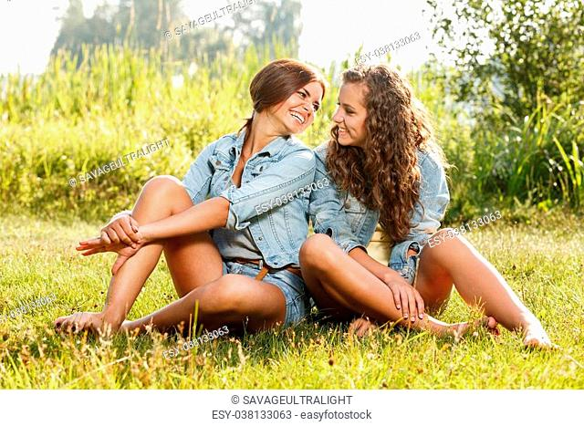 two girlfriends in jeans wear sitting on grass looking at each other