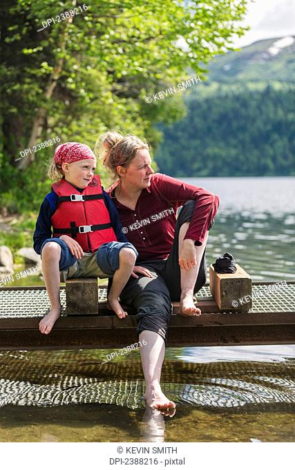 A mother and daughter sits on a dock looking out over Byers Lake, soaking their bare feet in the water, Denali State Park; Alaska, United States of America