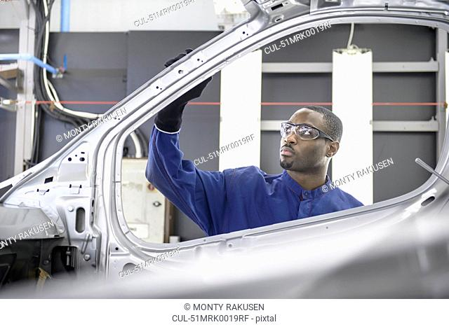 Worker inspecting car in factory