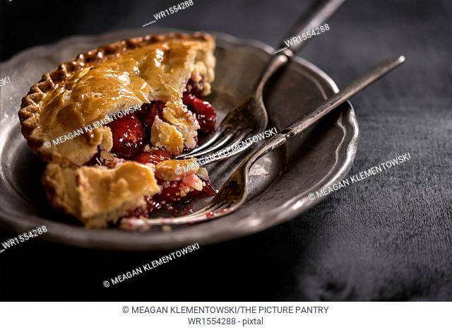 Small cherry pie on metal plate with antique forks. Dark, moody setting