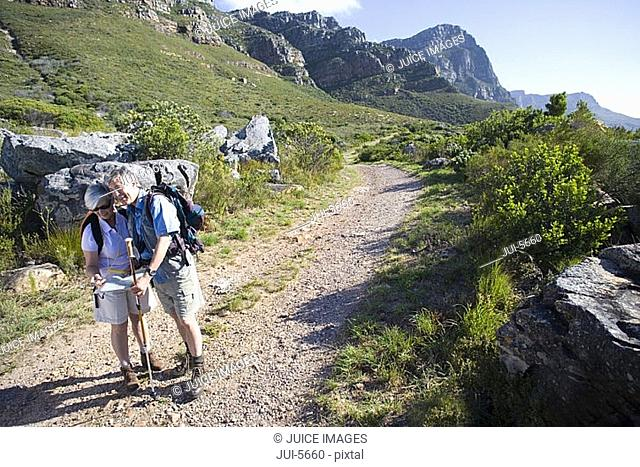 Mature couple, with rucksacks, hiking on mountain trail, looking at map, man leaning on hiking pole