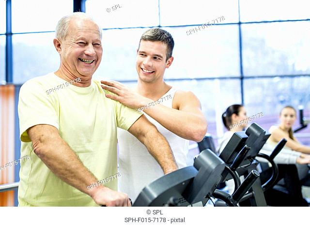 MODEL RELEASED. Young man assisting senior man while exercising on exercise bike in gym