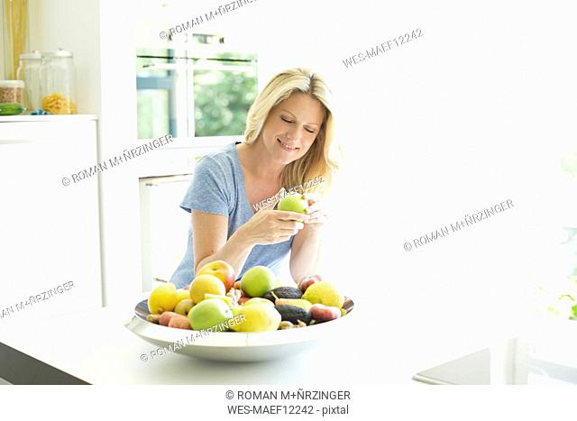 Smiling woman at home taking apple from fruit bowl