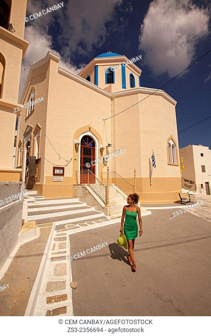 Woman walking around a colorful church in Hora, Serifos, Cyclades Islands, Greek Islands, Greece, Europe