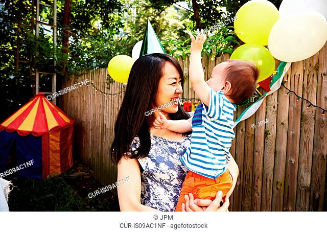 Mother wearing party hat holding baby boy at birthday party