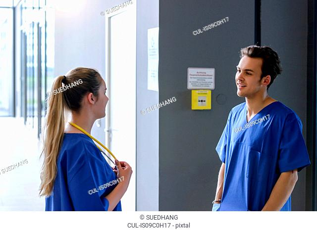 Male and female junior doctors chatting in hospital corridor