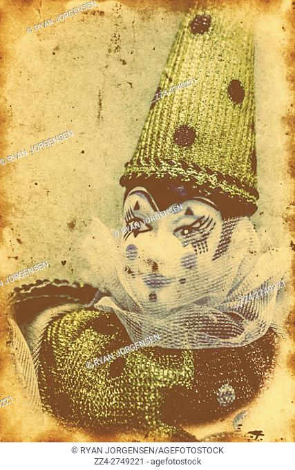 Vintage circus postcard with an antique performing arts porcelain clown on old paper texture