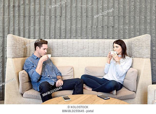 Caucasian couple relaxing on sofa drinking coffee