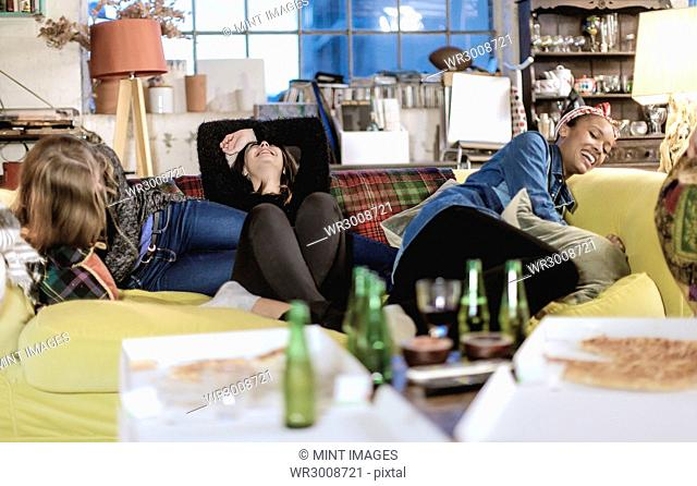 Three young women sitting on a sofa, laughing, pizza and beer bottles on coffee table