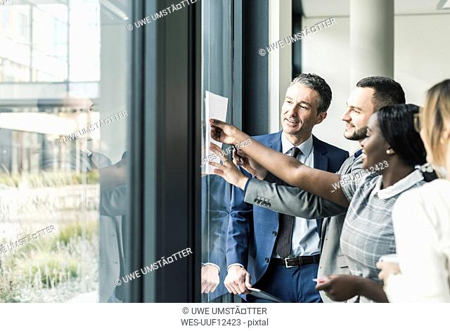 Smiling business people talking in office at the window