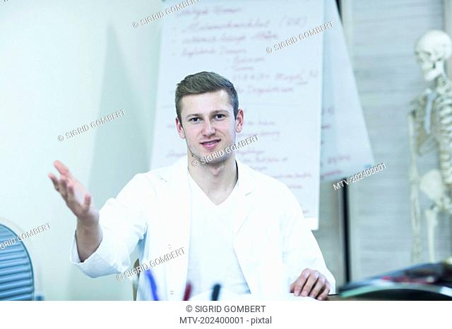 Portrait of a young doctor explaining about skeleton in his office, Freiburg Im Breisgau, Baden-Württemberg, Germany