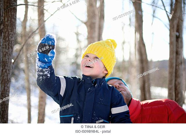 Man and son looking up in snow covered forest