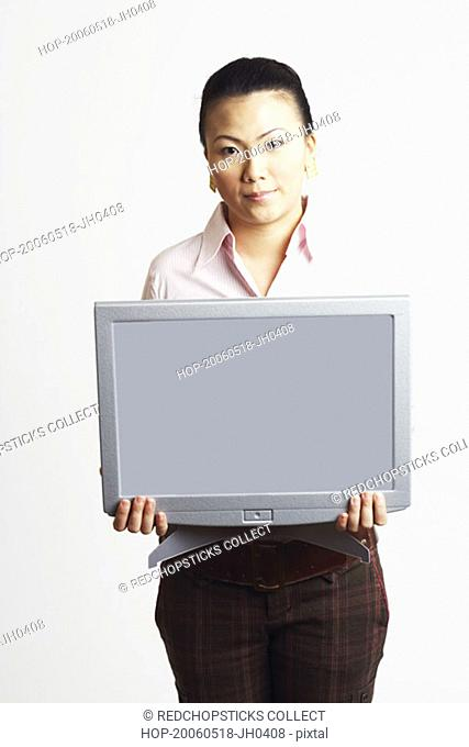 Portrait of a businesswoman holding the model of a computer monitor with progress reports