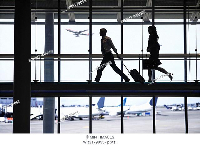 Businessman and business woman running to catch an airplane on an airport walkway