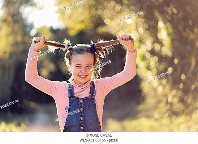 Portrait of laughing girl pulling her hair