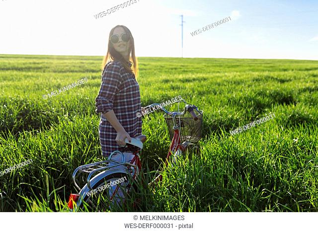 Young woman with bicycle standing in wheat field