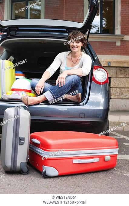 Germany, Leipzig, Woman sitting at back of car, suitcase in foreground