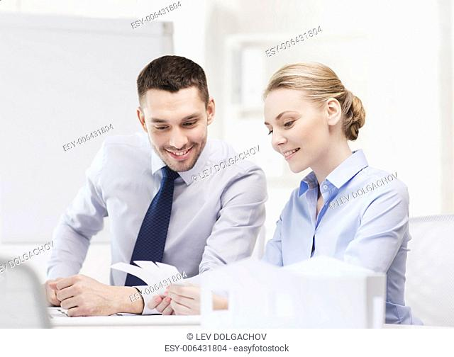 business, architecture and office concept - smiling businessman and businesswoman looking at color samples at office