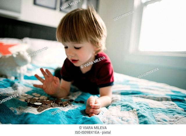 Boy counting coins on bed
