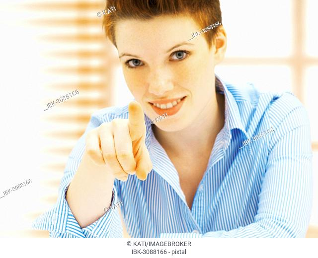 Businesswoman in an office, smiling, pointing forward