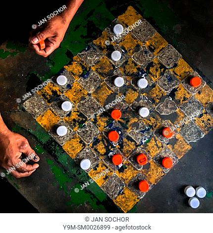 Hands of Salvadoran man are seen resting on the table while playing checkers on an outdoor checkerboard table in the park in San Salvador, El Salvador