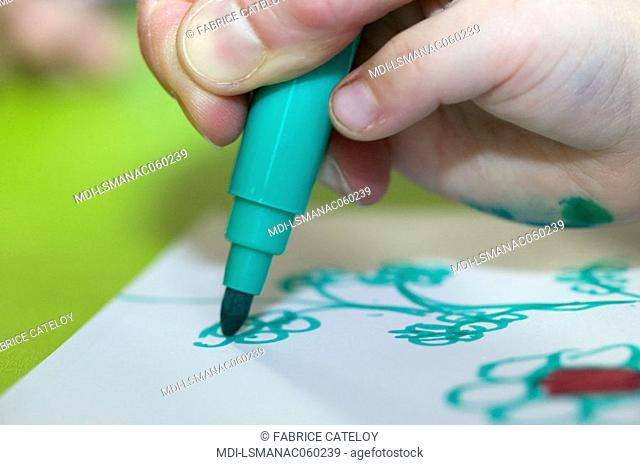 Adult's hand learning to a child how to draw