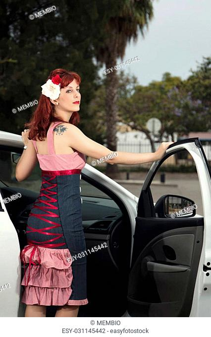 View of pinup young woman in vintage style clothing next to a white car