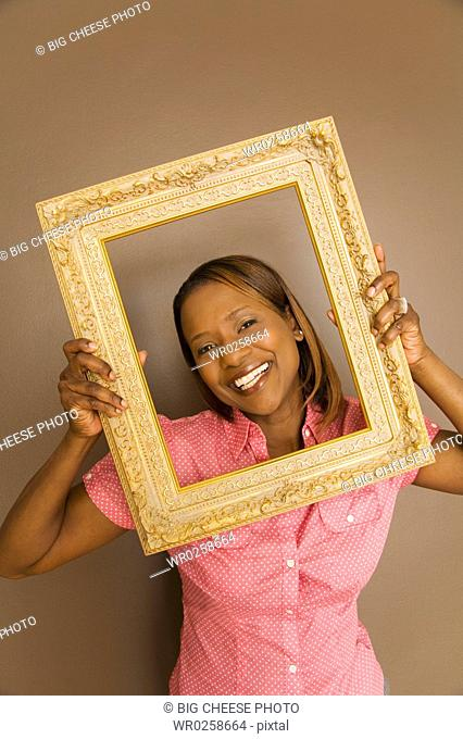 African woman looking through picture frame