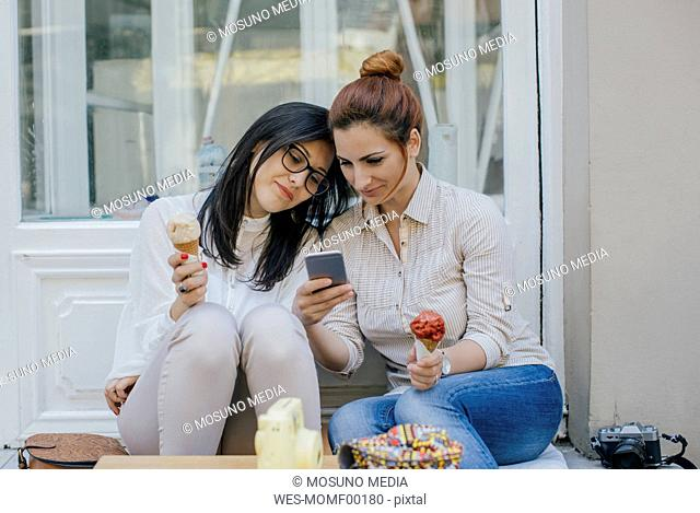 Two friends with ice cream and cell phone in the city