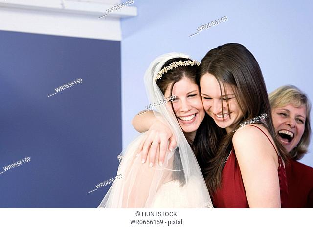 Friend embracing young bride