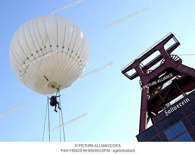 29 June 2019, North Rhine-Westphalia, Essen: A visitor of the extra shift at Zeche Zollverein is blown up with a helium balloon