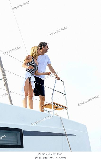 Mature couple making holidays, sailing on a catamaran
