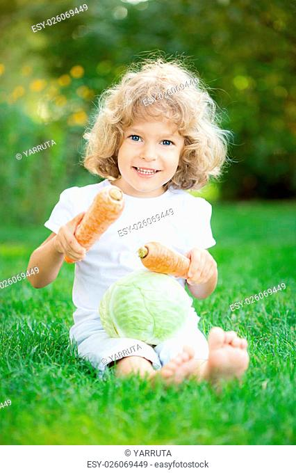 Happy smiling child with vegetables sitting on green grass in spring park. Healthy lifestyles concept