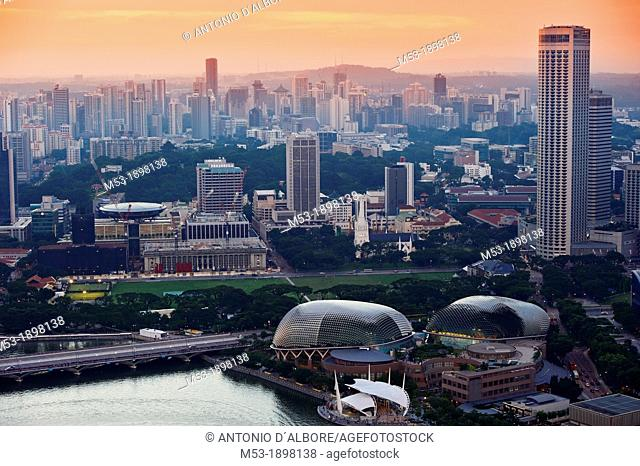 Aerial view of Singapore at sunset  The round shaped building in foreground is the Esplanade theatre and the water is marina bay reservoir