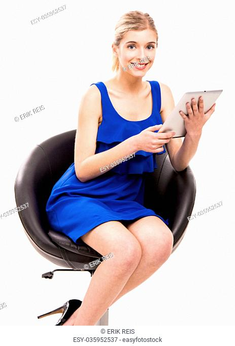 Beautiful woman sitting on a chair working with a tablet, isolated over white background