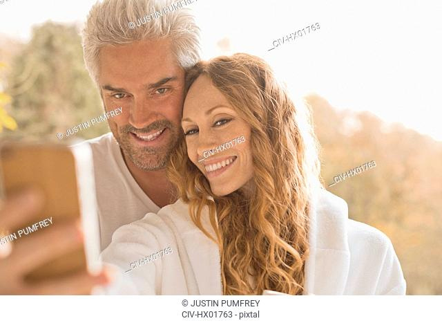Affectionate couple smiling taking selfie with camera phone outdoors