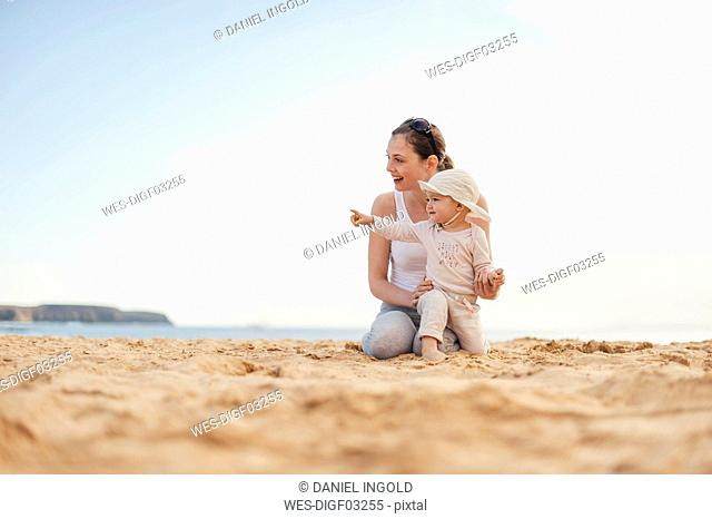 Happy mother with little daughter on the beach