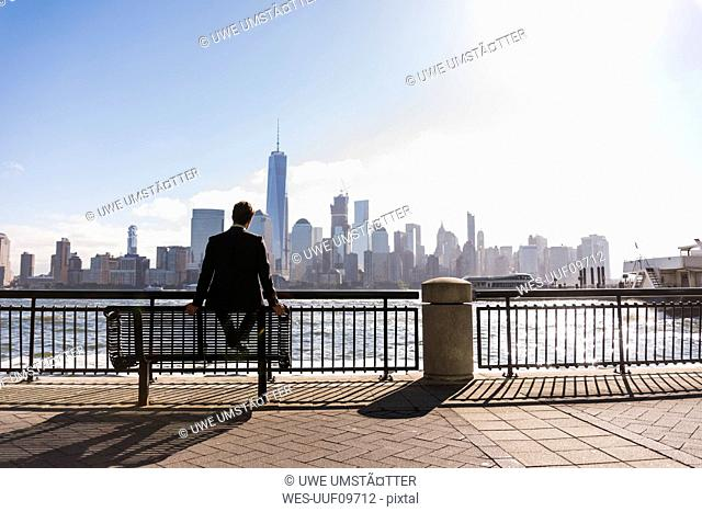 USA, man sitting on bench at New Jersey waterfront with view to Manhattan